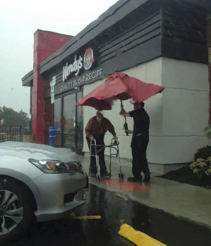 Сотрудник Венди Удаление Зонтик из таблицы Снаружи ходить пожилой человек к машине In The Rain