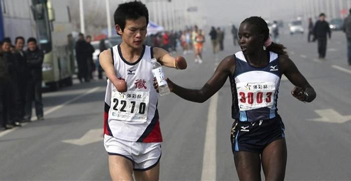 Женщина вручать бутылку воды к Fellow Runner без рук