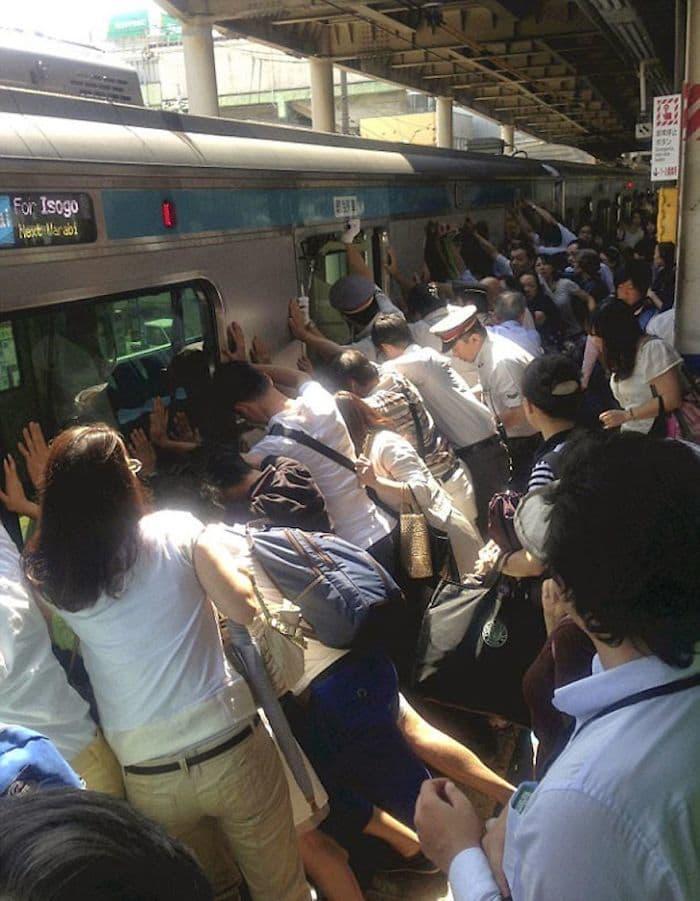 Люди работают вместе, чтобы помочь человеку, застрявших между платформой и поезд