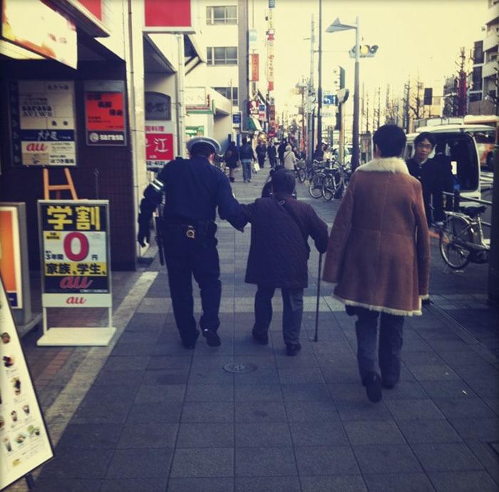 Японский офицер Помогая Старая женщина,