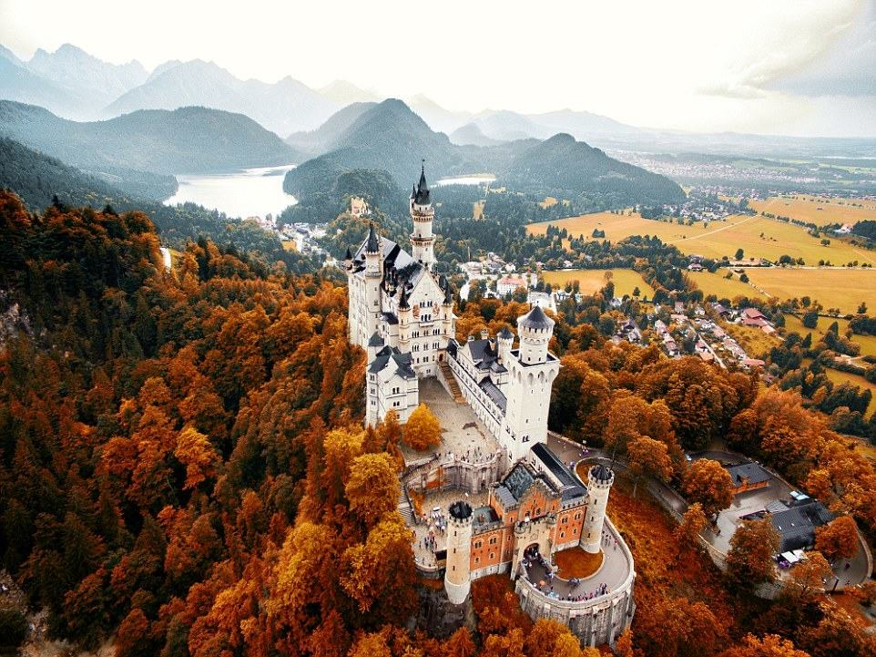 Uploads bearing the searchable tag include a fiery autumnal landscape featuring the fairytale-like Neuschwanstein Castle, captured by @jacob