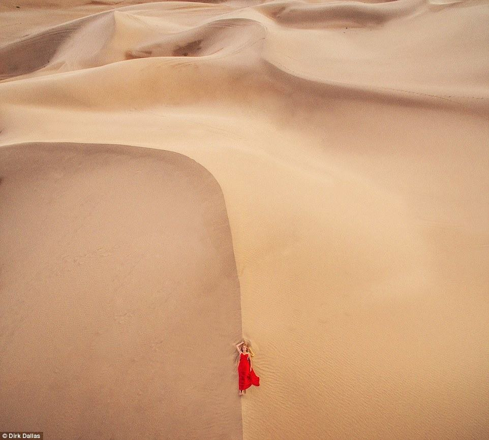 Dirk Dallas (@dirka) who created the hashtag features some of his own work in the mix including this image of a woman in a striking red dress in lying in the desert
