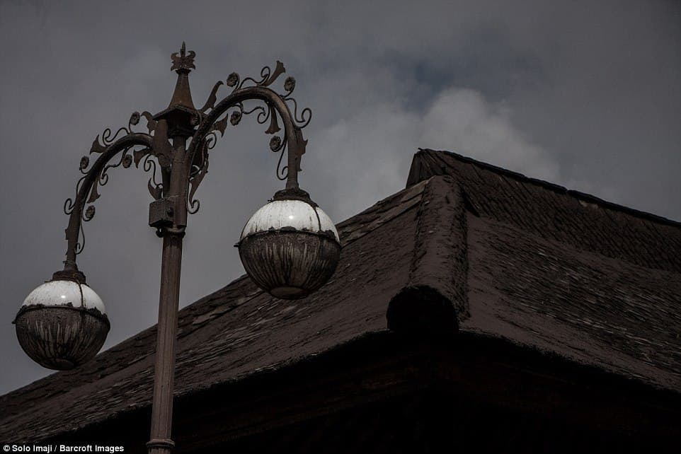 Ash has plastered the roof of a nearby temple and covered the lamp posts outside as darkness sweeps over the area