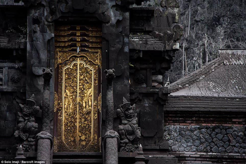 The images, captured by local photographer Solo Imaji at Pura Pasar Agung, show the contrast of the golden temple doors with the blackened remains of the ash clouds