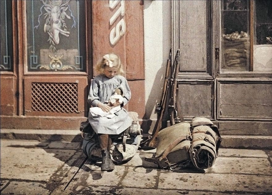 A Girl Holds A Doll Next To Soldiers