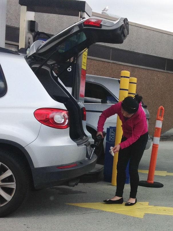 Женщина на станции с использованием бензина для очистки бампера