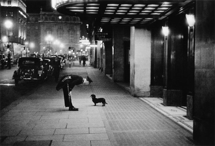 A Hotel Commissionaire Talking To A Small Dachshund Dog In Piccadilly Circus, London, 1938