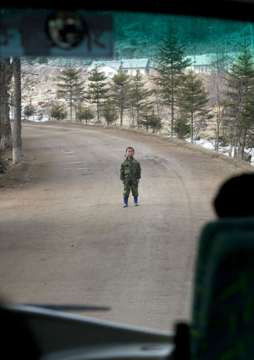 A Rare Example Of An Undisciplined Kid In North Korea. The Bus Was Driving In The Small Roads Of Samijyon In The North, When This Kid Stood In The Middle Of The Road