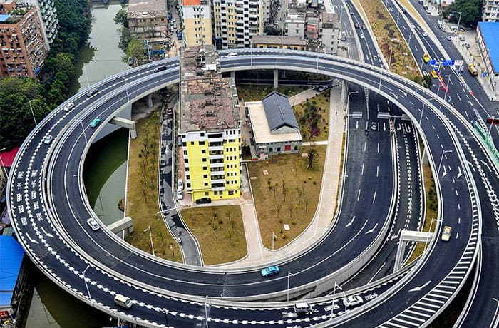 In Guangzhou, The Authorities Have Had To Build A Ring Road Around This Block Of Flats Because Three Families Would Not Budge