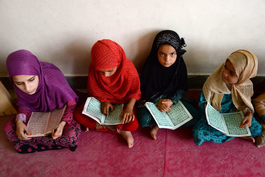 Afghan students who have lost their parents following suicide bomb attacks study the Qur