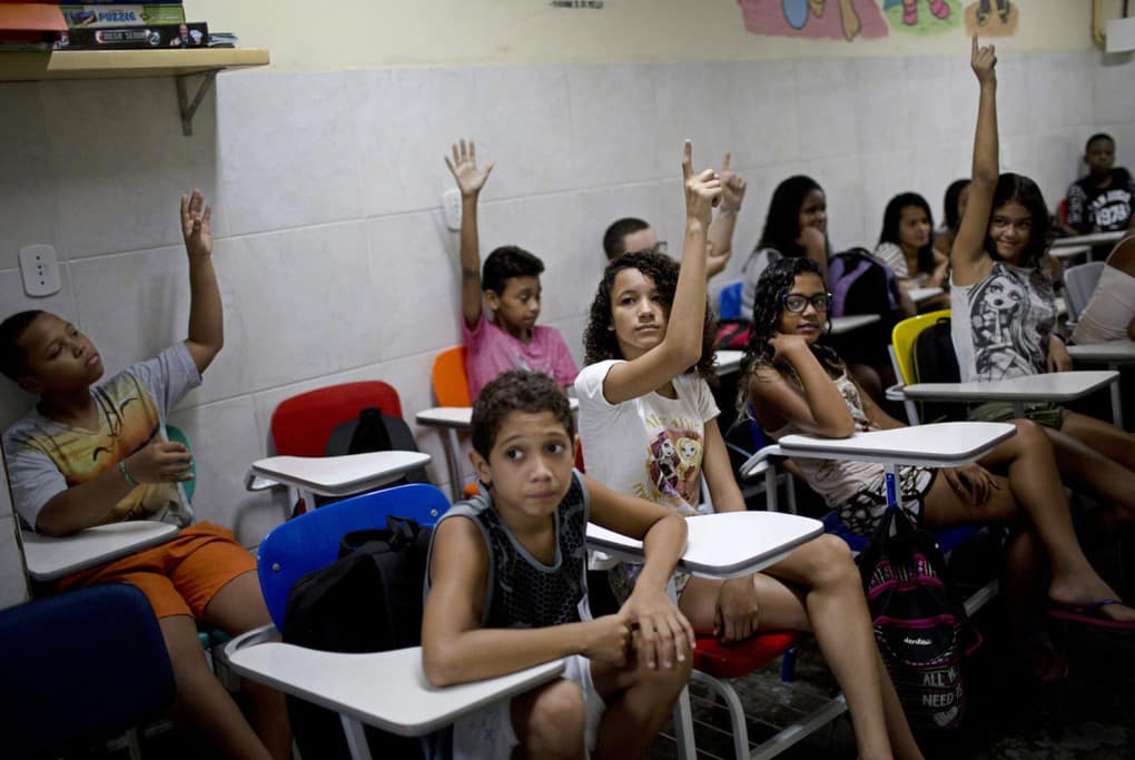 Students raise their hands after being asked how many had lost a family member to gun violence at the Projeto Uere special needs school in Rio de Janeiro on April 5.