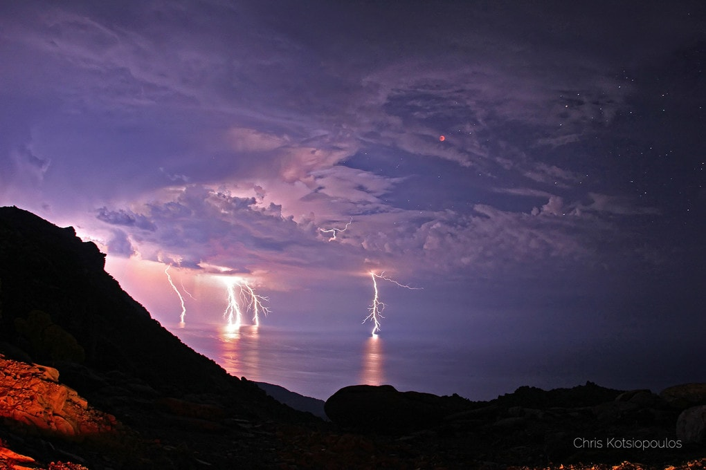 """Lightning Eclipse from the Planet of the Goats"" – clouds part during a thunderstorm to reveal a lunar eclipse on a Greek island, Ikaria, in an area known locally as the Planet of the Goats. This was one of NASA"