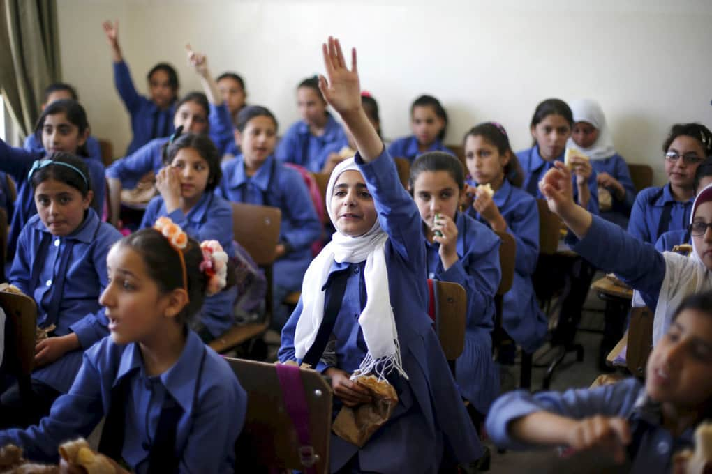Students raise their hands and eat a meal distributed by a World Food Program project, created to provide healthy meals to students and encourage good eating habits, at the Hofa Al-Mazar school in Irbid, Jordan, on April 26, 2016.