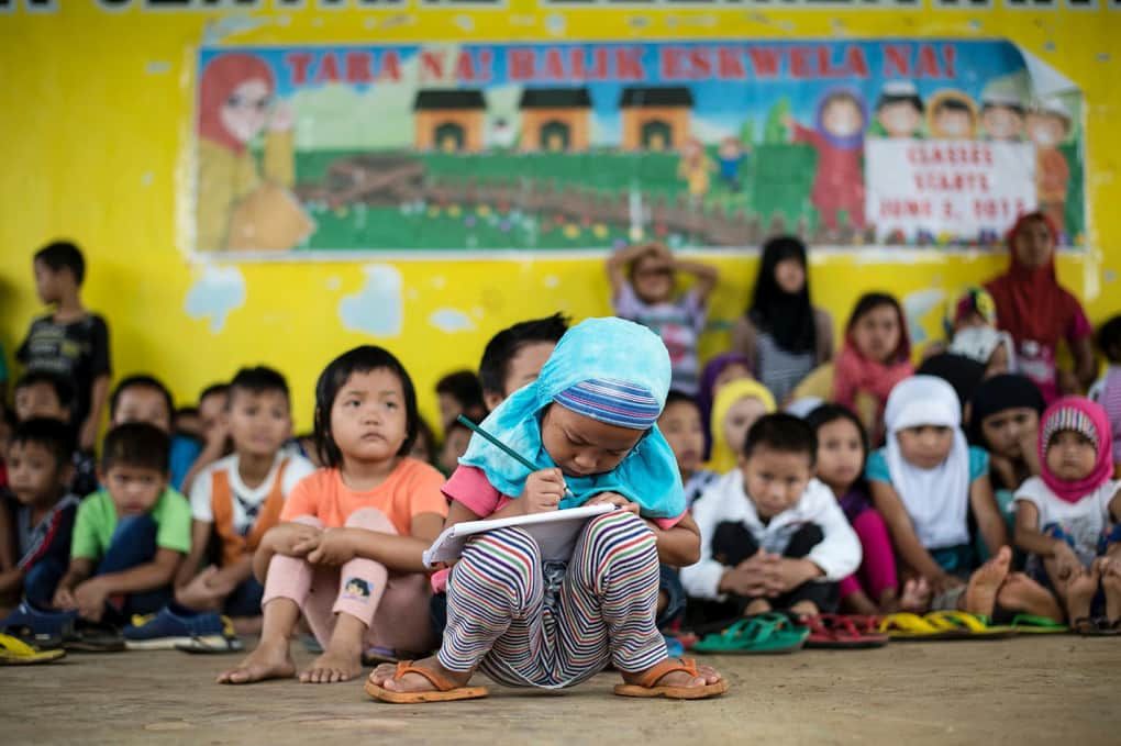 Johainah Nasrodeng, 5, writes in her notebook at a makeshift classroom for student evacuees at the Pantar Central Elementary School in Pantar, in the province of Lanao del Norte, Philippines, on June 6.