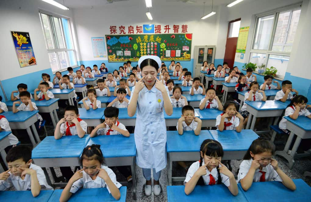 A hospital staff member teaches primary school children how to do eye exercises in Handan, China, on June 5.