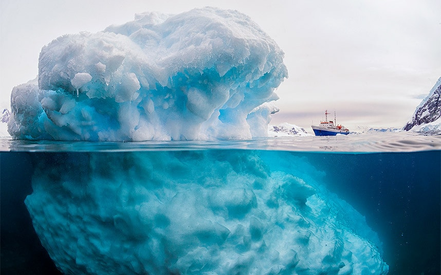 A 'giant' iceberg dwarfs a 3,000 tonne ship. The photograph is actually an optical illusion, with the block of ice in the foreground only reaching 6ft above sea level