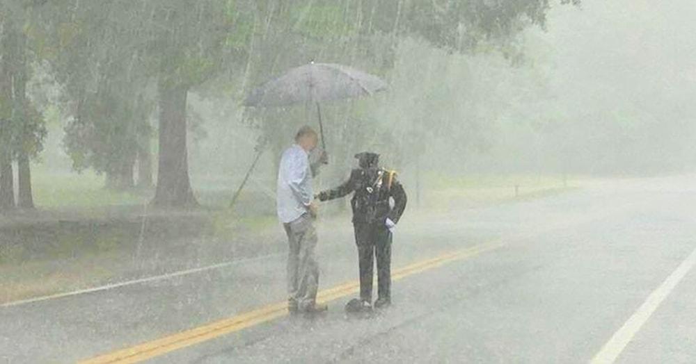 Люди удивились, увидев полицейскую, стоявшую на дороге под дождём. А узнав о причине, удивились ещё больше